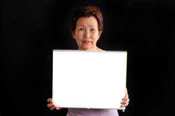 ホワイトボードを持っている高齢の女性