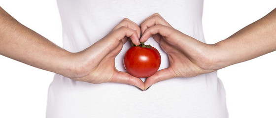 smiling woman with organic food showing heart shape with hands