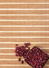 Red beans in basket on bamboo mat background