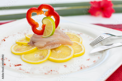 Fish Carpaccio on lemon,  decorated with red bell pepper slice a