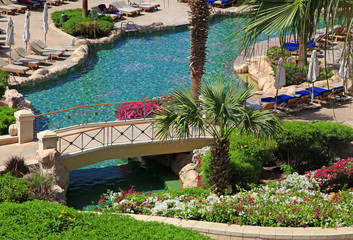 beautiful resort swimming pool with sun chairs, bridge and flowe