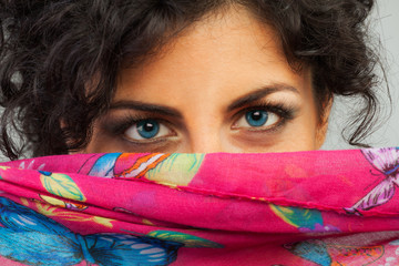 Beautiful woman with blue eyes hiding behind a scarf