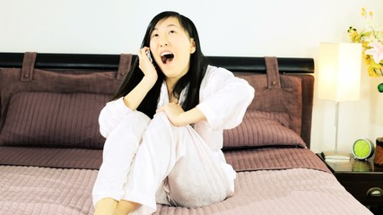 Happy Chinese woman laughing on the phone in bed