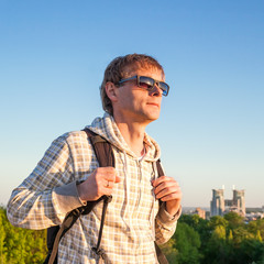 Happy man hiker holding backpack and looking at the sunset