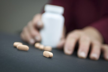 Hands Of Woman Deformed From Rheumatoid Arthritis holding pills