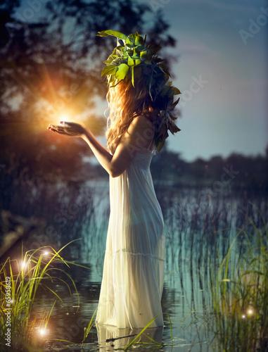 Fantasy girl taking magic light. Mysterious night scene