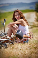 beautiful smiling girl sitting next to bike, summer time