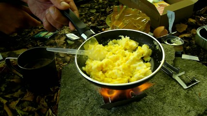 Cooking in nature on small camping cooker, scrambled eggs on pan