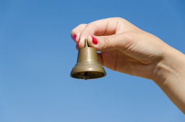 Woman hand red nails hold iron bell on blue sky