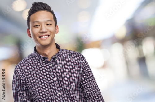 Handsome young asian man smiling wearing a plaid shirt - 65959261