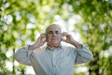Blissful senior man listening to music