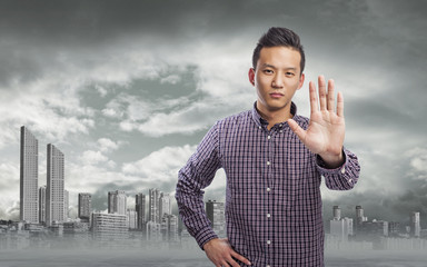 young asian man doing stop gesture with hand