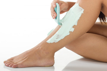 close up of woman shaving her legs with razor