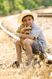 lonely orphan child sitting on the railroad poster