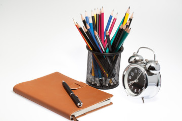 notebook with pen box and clock