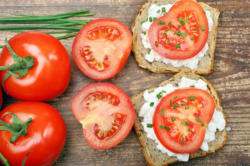 Sandwich with cottage cheese and tomato on wood background
