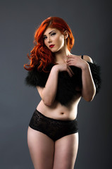 Curvy redhead in sexy lingerie isolated over gray background