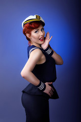 Pin up model in sailor costume isolated on blue background