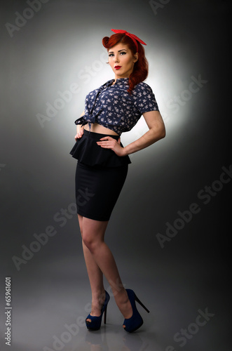 Full length portrait of a pin up girl posing with hands on waist