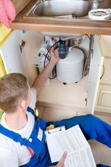 Young handsome plumber plumbing repairs. Replacement water filte
