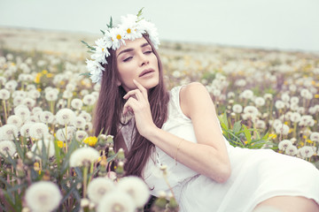 Alluring woman lying on a meadow full of dandelions
