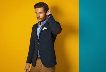 Fashionable man wearing jacket and posing