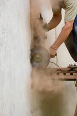 Мужчина разрезает стену
