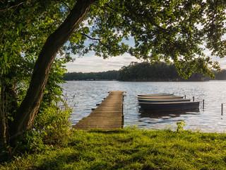 Ein Steg und Boote am See.