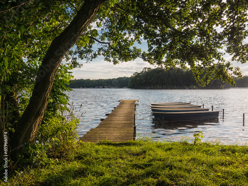 canvas print picture Ein Steg und Boote am See.