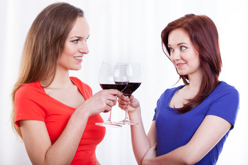 Beautiful female friends raising glasses of red wine