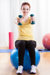 Girl sitting on exercise ball and lifting weights