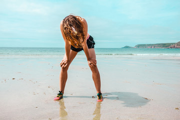 Athletic young woman resting after running on beach