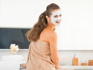 Smiling young woman wearing facial cosmetic mask