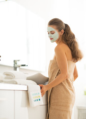 Young woman wearing facial cosmetic mask in bathroom