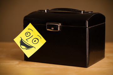 Post-it note with smiley face sticked on a jewelry box