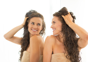 Happy young woman with long wet hair looking in mirror