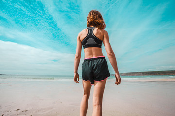 Athletic young woman standing on the beach