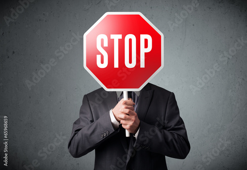 Leinwanddruck Bild Businessman holding a stop sign