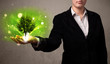 Glowing tree growing in the hand of a businesswoman