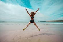 Mujer joven que hace la estrella salta en la playa
