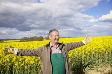 Farmer with outstretched arm at the rape field