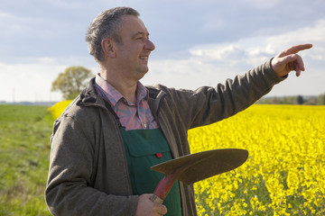Farmer with shovel controls his canola field