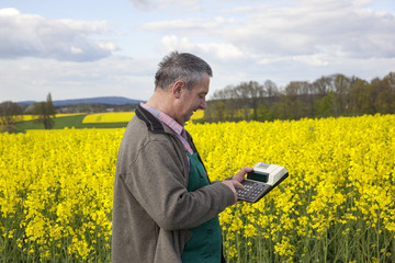 Farmer with calculation engine in the rape field