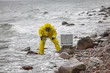 specialist in protective suit taking sample of water rocky shore