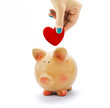 Hand deposit red heart in piggy bank isolated