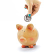 Hand depositing coin with British pound sign in piggy bank