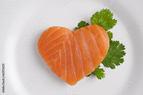 Heart shaped salmon on white plate
