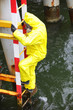specialist  protective suit  on ladder over the sea