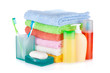 Two colorful toothbrushes, cosmetics bottles, soap and towels