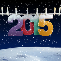 Number 2015 hanging on a clothesline in a night wintry bac